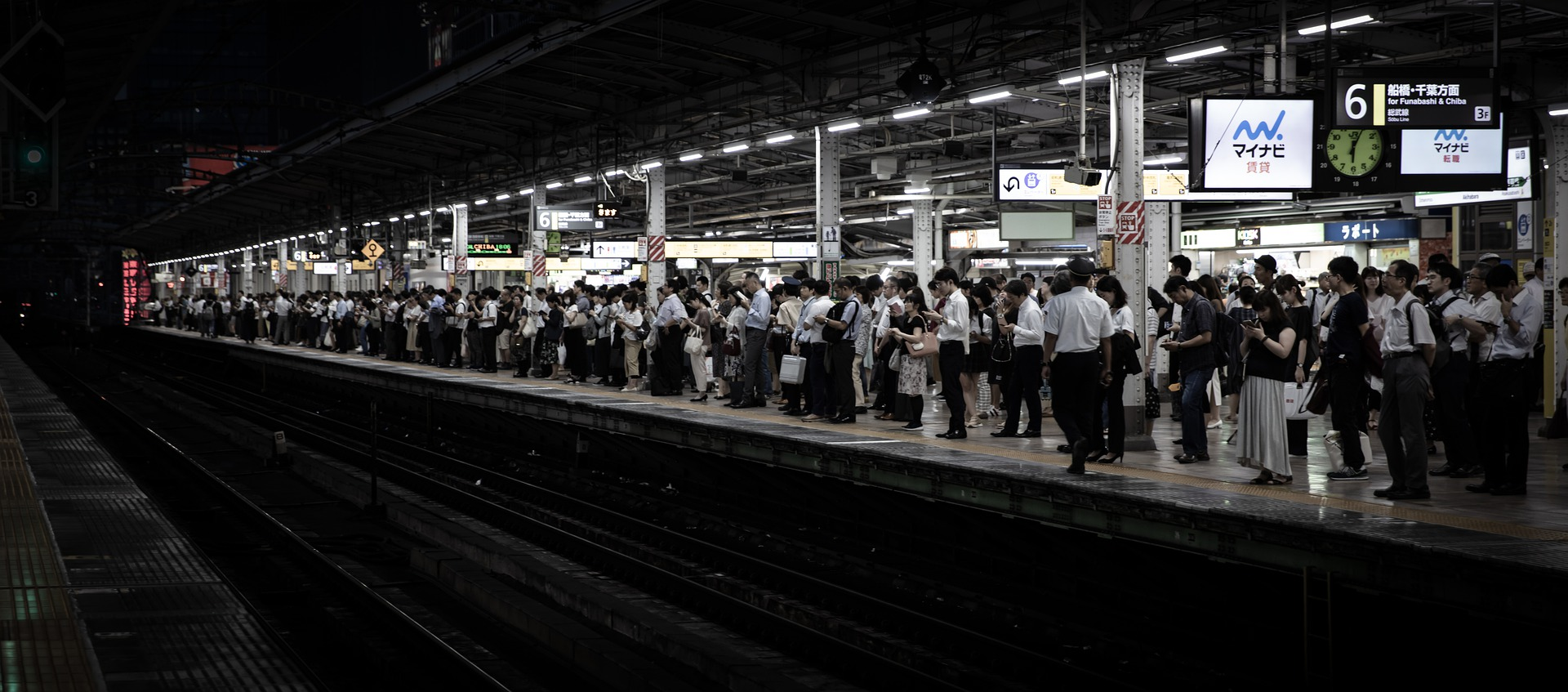 A Tokyo train platform with workers waiting to board a train.
