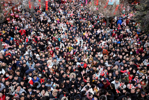 Tourists crowd the Millennium City Park to get red pocket money from Chinese entertainers dressed as the God of Wealth, also known as Caishen, to receive blessings on the fifth day of the Chinese Lunar New Year or Spring Festival in Kaifeng city
